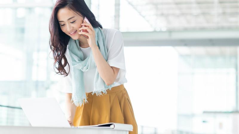 パソコン前で立ち上がって電話する女性