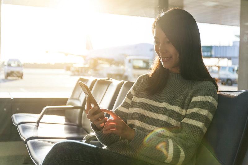 空港でスマホを見る女性