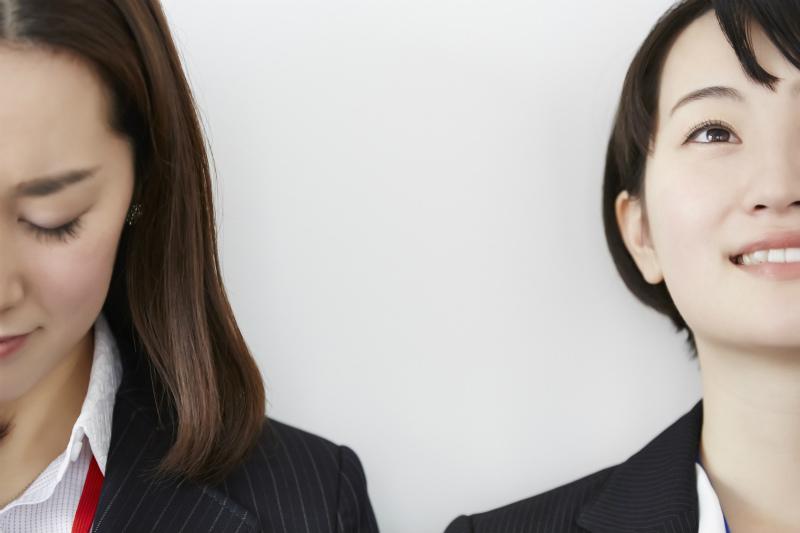 顔をふせる女性と顔を上げる女性