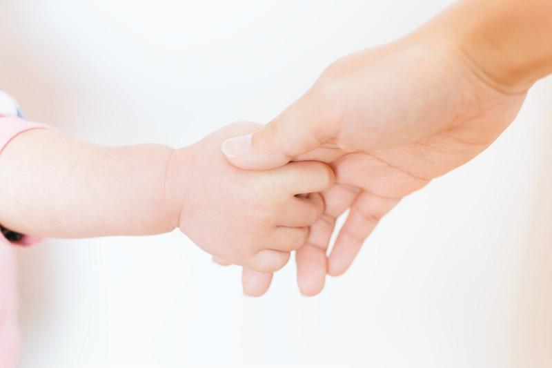 新生児の手を握る母の手